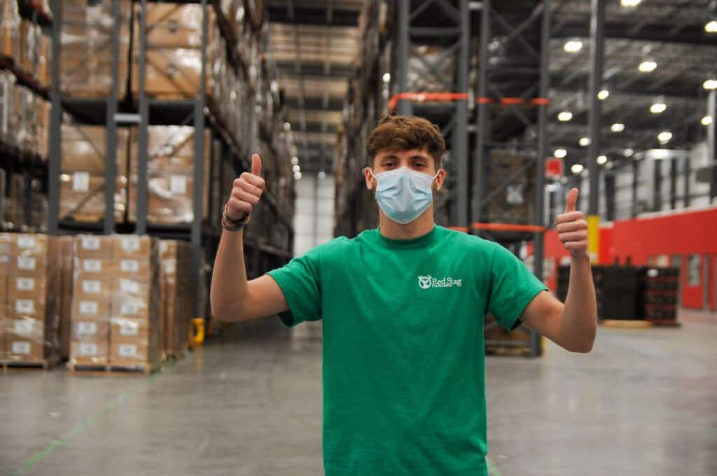 thumbs up happy worker in warehouse