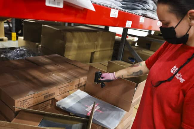 warehouse employee scans a barcode with a handheld scanner