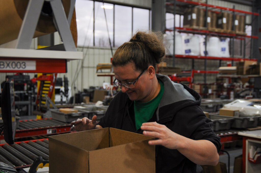 Worker at a direct fulfillment center packs a box